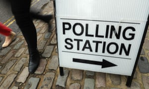 A person walks past a sign for a polling station.