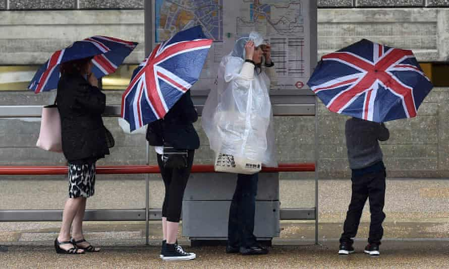 People shelter from the rain at a bus stop in central London