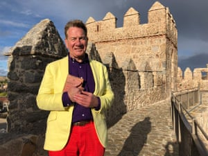 """Michael Portillo on the Walls of Ávila, Spain, wearing a """"yellow jacket, purple shirt and tomato trousers"""""""