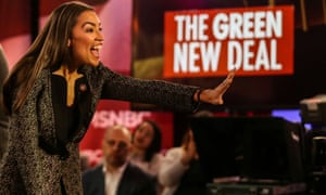 Alexandria Ocasio-Cortez greets the audience at a televised town hall event on the Green New Deal in the Bronx.