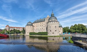 Orebro castle reflecting in water on sunny summer day in city Orebro, Sweden