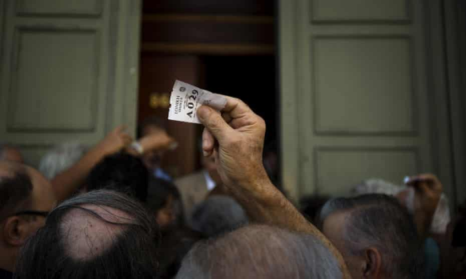 Pensioners wait outside the main gate of the national bank of Greece.