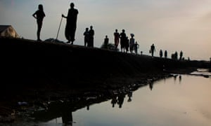 Refugees from Leer walk along the edge of a drainage chanel in in the in Protection of Civilian (POC) camp in the evening light in Bentiu, South Sudan