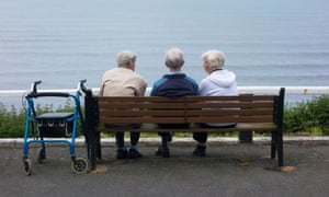 Two elderly men and an elderly woman sitting on a bench overlooking the sea in Saltburn by the Sea, North Yorkshire
