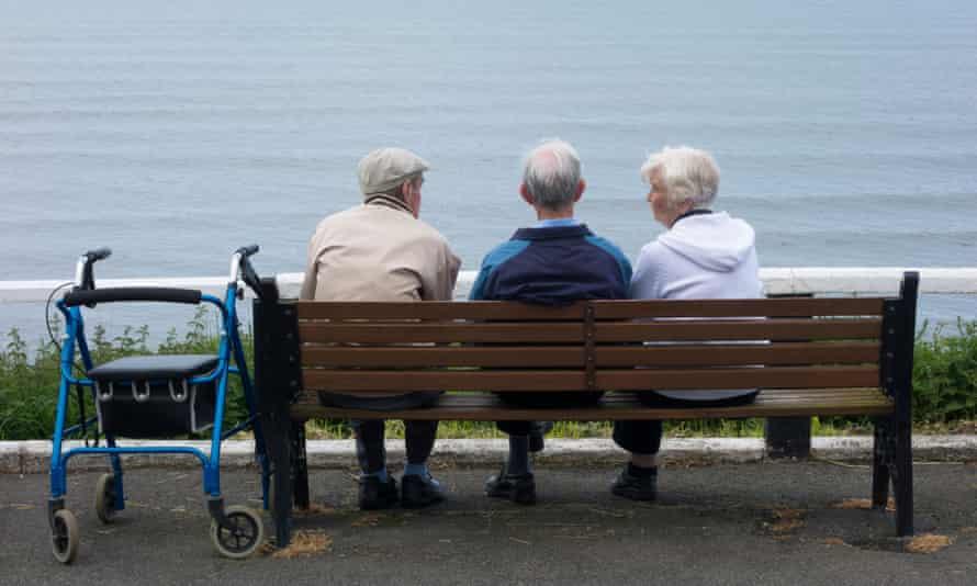Three older people on seaside bench