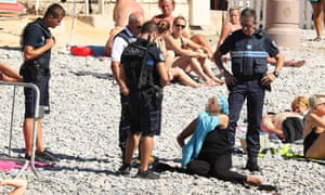 Police accosting a woman in a burkini on the beach in Nice.