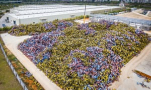 A crane unloads dumped shared bikes from trucks at Xiamen, China. So far, the city authorities have collected more than 120,000 abandoned shared bikes.