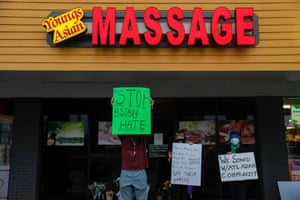 People hold signs outside Young's Asian Spa following the deadly shooting.