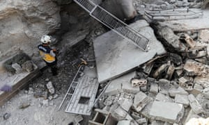 A member of the Syrian Civil Defence, also known as the 'White Helmets', walks through the wreckage of their centre, destroyed by regime bombing.