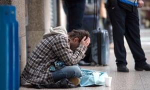 A homeless man begs in a London street