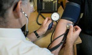 A GP checks a patient's blood pressure using a stethoscope