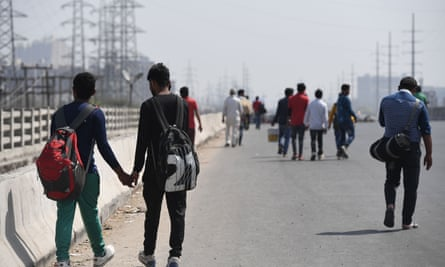 Workers returning home wait for transportation along the Delhi-Meerut Expressway following a lockdown order on 23 March 2020.