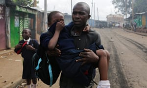 A man carries a schoolgirl overcome by tear gas and smoke from burning barricades during running battles between police and protesters in the Kibera slum of Nairobi.