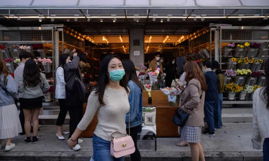 People wearing face masks walk along a street in the Yeonnam district of Seoul