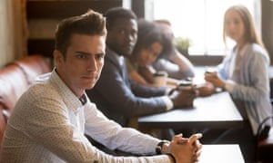 Diverse friends looking at frustrated man sitting alone in cafe