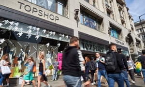 Shoppers walking past a branch of clothing retailer Topshop on Oxford Street in central London.