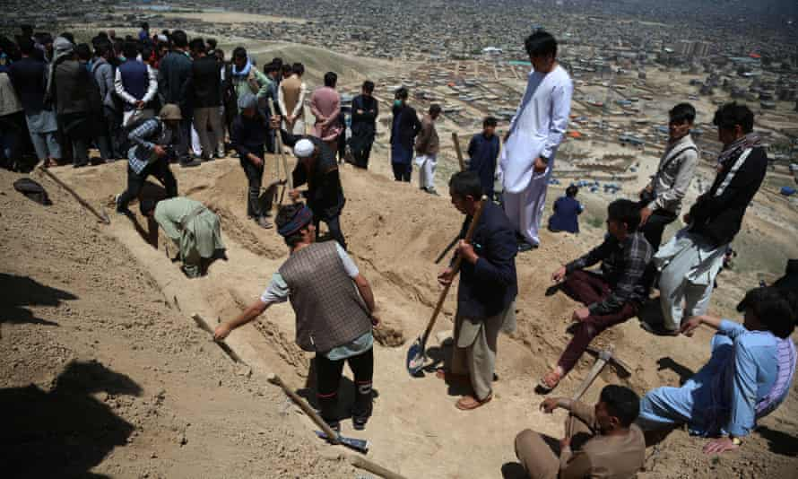 People dig graves for the dozens of victims, mainly schoolgirls, of bomb blasts in Kabul, Afghanistan, on Saturday.