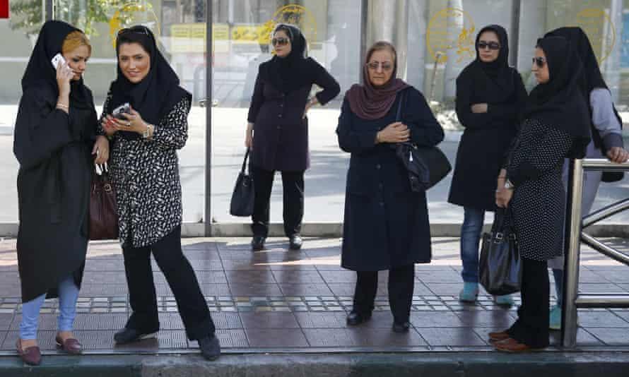 Women wait for a bus in central Tehran.