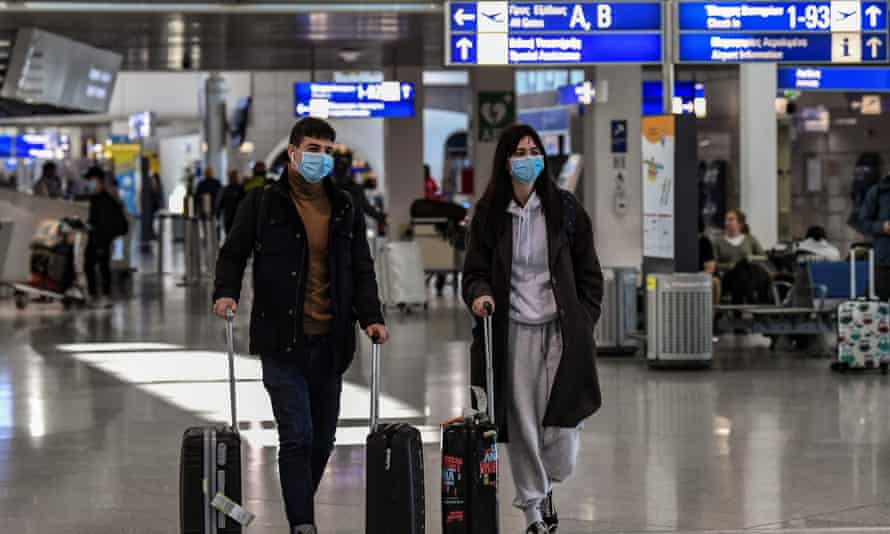 Travellers wearing protective masks in Athens international airport in March