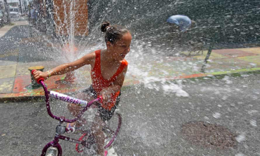 A person cools off in spraying water from a fire hydrant in the Kensington neighborhood of Philadelphia