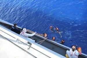 People on an Italian navy vessel pulls refugees aboard