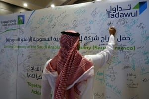 A man signs on a board at the Saudi Stock Exchange (Tadawul) following the debut of Saudi Aramco's initial public offering (IPO) on the Riyadh's stock market, in Riyadh, Saudi Arabia, December 11, 2019. REUTERS/Ahmed Yosri NO RESALES. NO ARCHIVES.