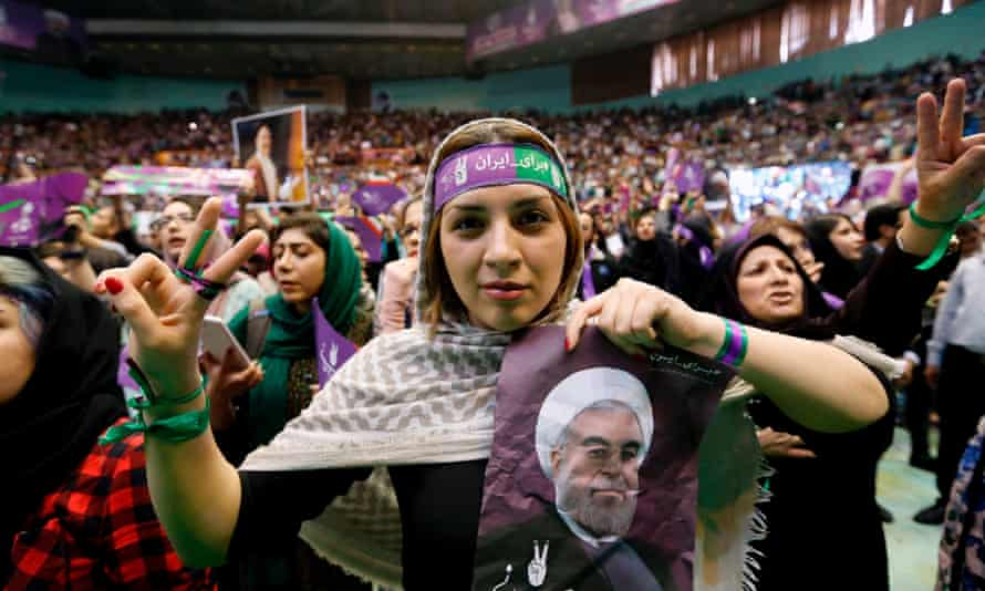 A supporter of presidential candidate Hassan Rouhani holds up his portrait during a campaign rally in Tehran on Saturday