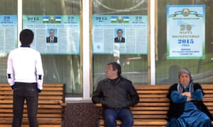 People look at election posters of presidential candidates in Tashkent in March.