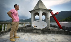 A lay leader on a church roof after government workers cut down the building's cross in Zhejiang province.