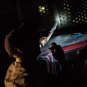 A policeman confiscates a knife during a night patrol