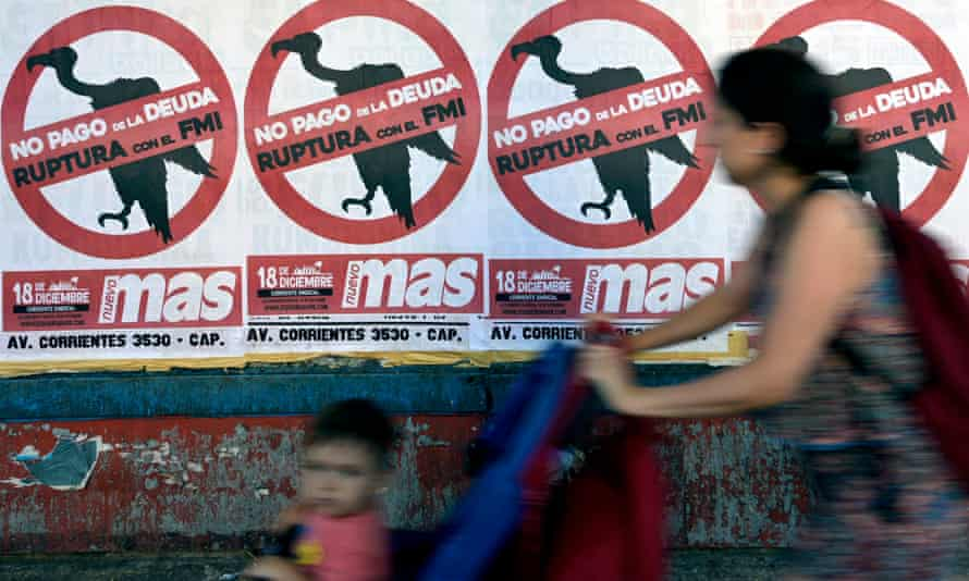 A resident of Buenos Aires pushes her toddler past posters portraying the International Monetary Fund as a vulture.