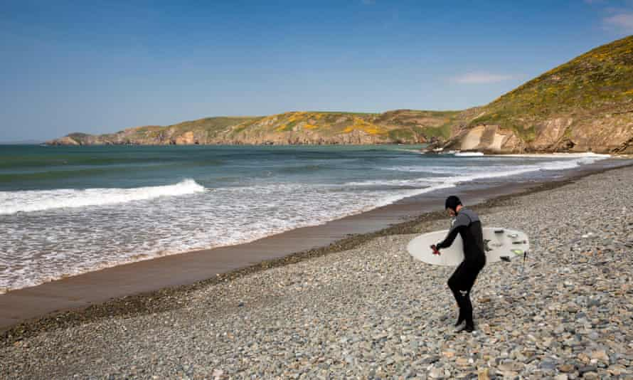 UK, Wales, Pembrokeshire, Newgale, surfer wearing wetsuit descending pebbly beach to seaJ9NPWB UK, Wales, Pembrokeshire, Newgale, surfer wearing wetsuit descending pebbly beach to sea