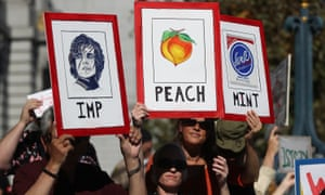 Attendees at a rally addressed by Steyer hold signs calling for the impeachment of Donald Trump.
