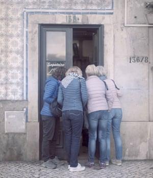 Tourists look into a shop in Lisbon's Graça neighbourhood.