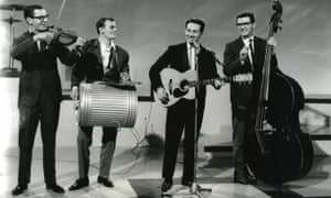Southern blues and country inflections … Lonnie Donegan plays guitar with his band in 1958.