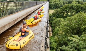 Jason leads the group of four, paddling individual  rafts, across the 'stream in the sky' on top of a viaduct.