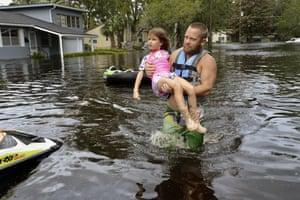 Tommy Nevitt carries Miranda Abbott, 6, through floodwater on the west side of Jacksonville