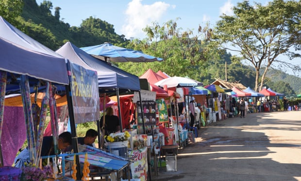 Food and souvenir stalls along the road to the Tham Luang cave complex. Image: The Guardian