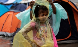 A migrant girl, part of a caravan from Central America trying to reach the US, wears a raincoat at a temporary shelter in Tijuana, Mexico.