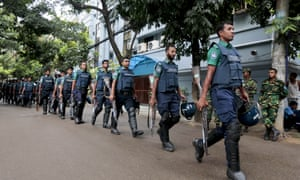 Bangladeshi policemen patrol the area around the site of the attack in Dhaka on 2 July.