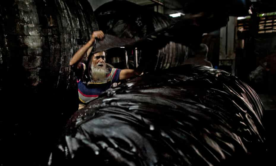 Abu Talib unloads leather hides from a vat of chemicals at a tannery in Dhaka