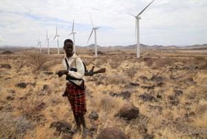 A Turkana herd boy carries his gun as he follows his goats near wind turbines at the Lake Turkana Wind Power project in Marsabit County, northern Kenya