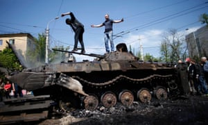 People stand on top of burnt-out armoured personal carrier near the city hall in Mariupol, eastern Ukraine.