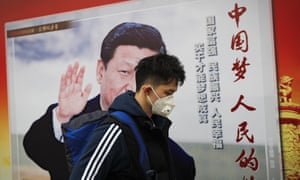 """A man wearing a mask for protection against pollution walks by a poster featuring Chinese President Xi Jinping and the words, in red, """"China Dream, People Dream"""", along a street in Beijing"""