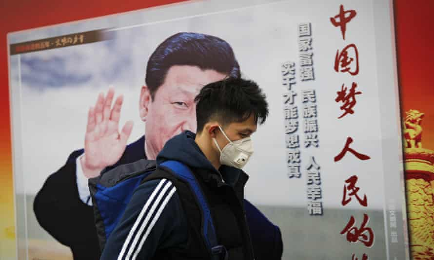 "A man wearing a mask for protection against pollution walks by a poster featuring Chinese President Xi Jinping and the words, in red, ""China Dream, People Dream"", along a street in Beijing"