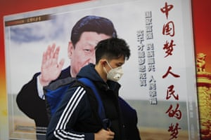 A man wearing a mask for protection against pollution walks along a street in Beijing.