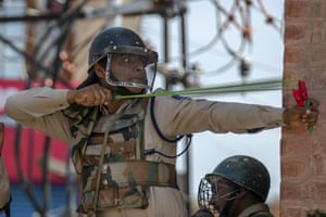 A paramilitary soldier uses a catapult to shoot glass marbles at Kashmiri protesters during a demonstration in Srinagar