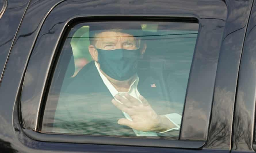 Donald Trump waves from the back of a car outside Walter Reed medical center in Bethesda, Maryland, on 4 October.
