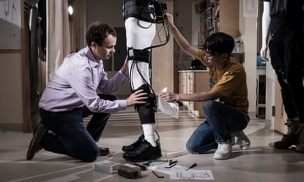 Conor Walsh and a colleague assemble an exosuit on a mannequin.