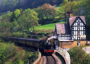 A steam locomotive passes the Tudor-style stationmaster's house at Berwyn.